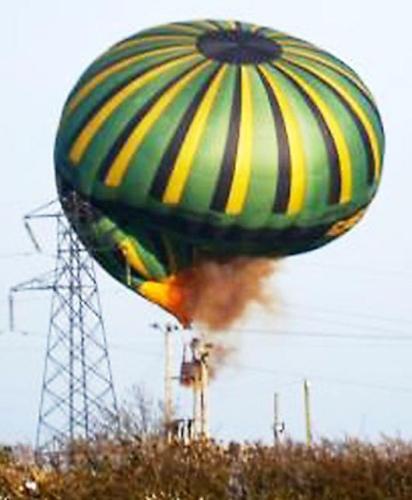 热气球缠绕在万伏高压电线上,冒着浓厚的烟火